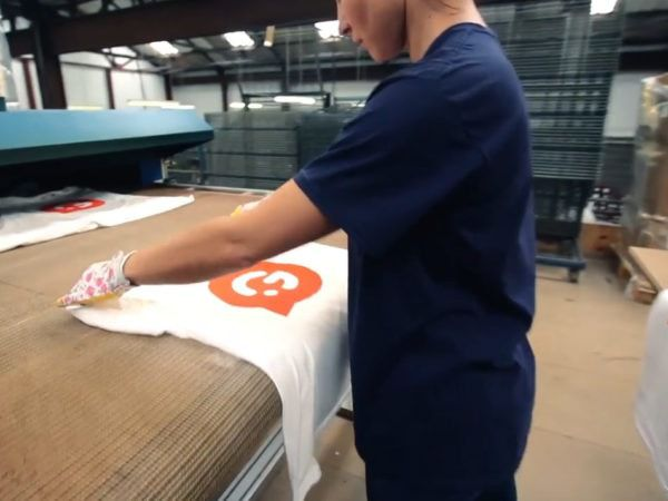 Person creating a screen printing sample with Garment Printing logo